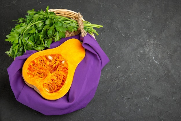 Vista superior de uma abóbora fresca com verduras dentro da cesta na mesa escura