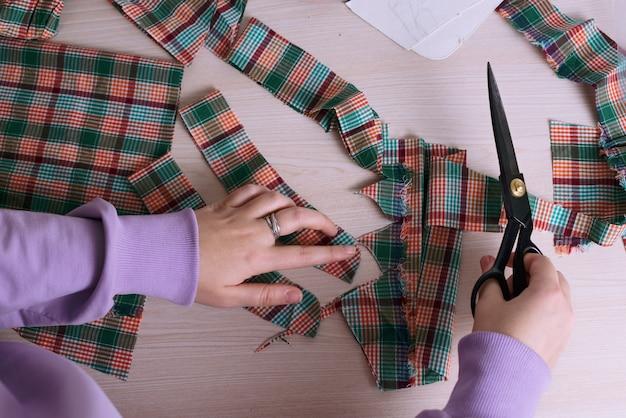 Vista superior de uma alfaiate cortando um tecido xadrez para fazer uma camisa
