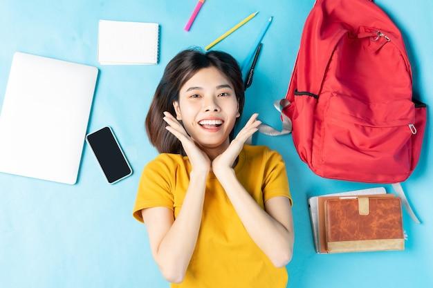 Vista superior de uma aluna feliz deitada sobre um fundo azul e olhando para a câmera