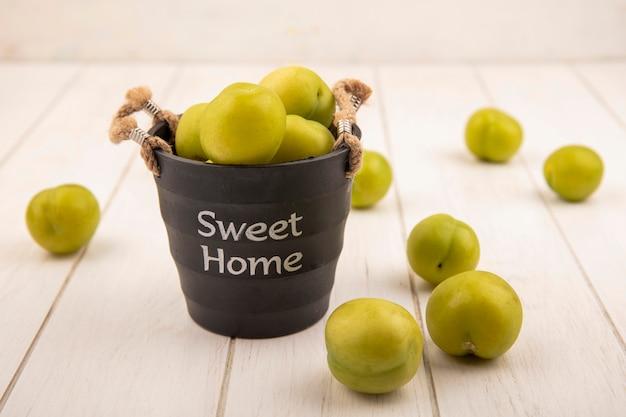 Vista superior de uma ameixa de cereja verde em uma cesta preta com ameixas de cereja verdes isoladas em um fundo branco de madeira