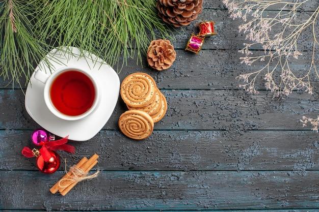 Vista superior de uma árvore de abeto de chá ao longe com cones e brinquedos de natal em bastões de canela e uma xícara de chá no pires