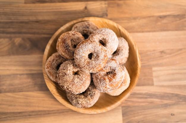 Vista superior de uma bandeja de donuts de açúcar caseiro recém-assados em uma mesa de madeira em uma cozinha
