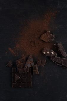 Vista superior de uma barra de chocolate escura caiu em pedaços