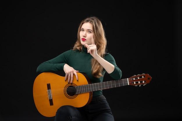 Vista superior de uma bela e ambiciosa musicista segurando o violão e chamando alguém no escuro
