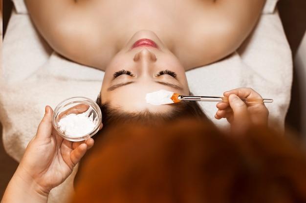 Vista superior de uma bela jovem inclinada sobre uma cama com os olhos fechados, enquanto um cosmetologista aplicando uma máscara branca com um pincel.