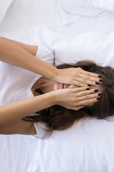 Vista superior de uma bela jovem sexy cobrindo o rosto enquanto estava deitada na cama