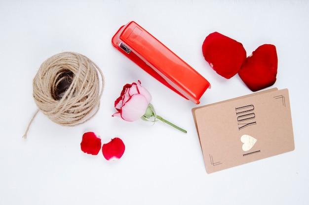 Vista superior de uma bola de corda pétalas de rosa vermelhas e flor rosa com pequeno cartão postal e grampeador em fundo branco