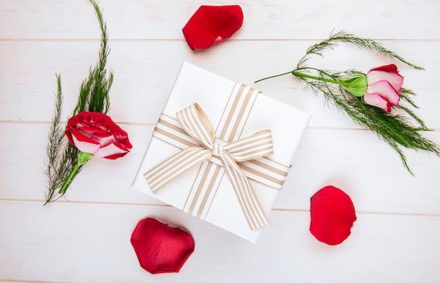 Vista superior de uma caixa de presente amarrada com laço e rosas de cor vermelha com pétalas espalhadas e aspargos no fundo de madeira branco