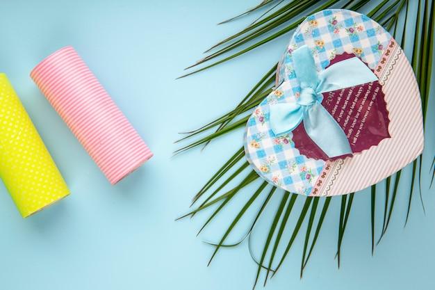 Vista superior de uma caixa de presente em forma de coração com folha de palmeira e rolos de fita adesiva sobre fundo azul