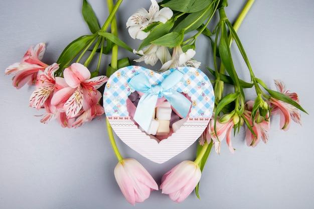 Vista superior de uma caixa de presente em forma de coração com marshmallow e alstroemeria cor de rosa e branco e flores tulipa na mesa branca