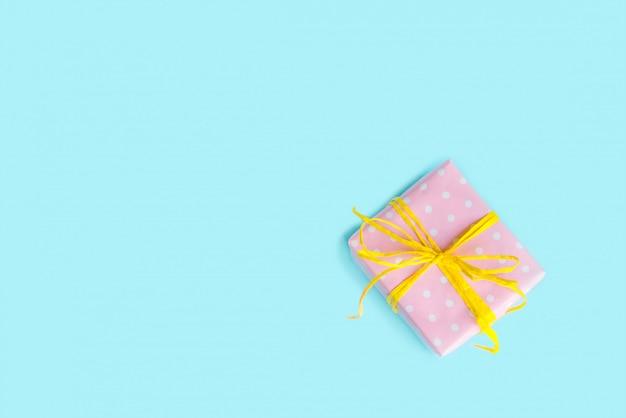 Vista superior de uma caixa de presente embrulhada em papel pontilhado rosa e laço amarelo amarrado sobre azul claro.