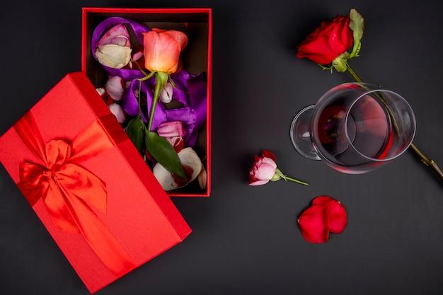 Vista superior de uma caixa de presente vermelha aberta com flor rosa e um copo de vinho tinto na mesa preta