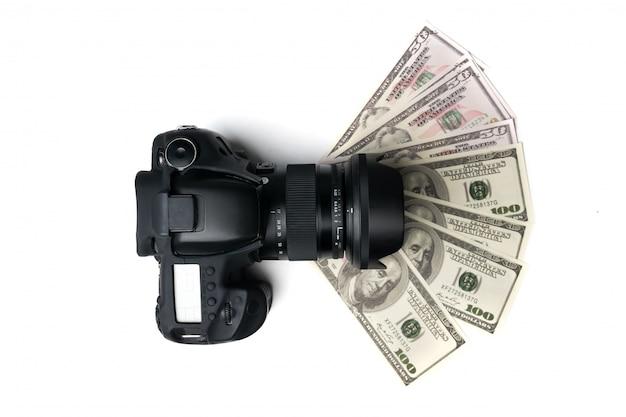 Vista superior de uma câmara digital preta nas notas de banco com fundo branco.