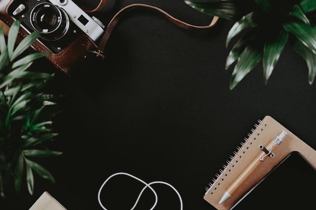 Vista superior de uma câmera de filme plano, caso um smartphone com bloco de notas de fones de ouvido e uma caneta esteja na superfície preta da mesa. conceito de espaço de trabalho de um artista ou aluno. espaço de publicidade