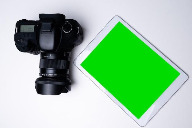 Vista superior de uma câmera digital preta e um tablet de tela em branco em uma tabela.