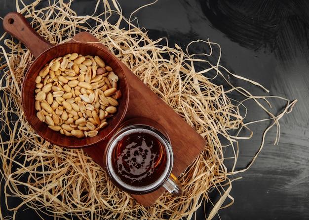 Vista superior de uma caneca de cerveja e amendoins em uma tigela na placa de madeira em palha no rústico, com espaço de cópia