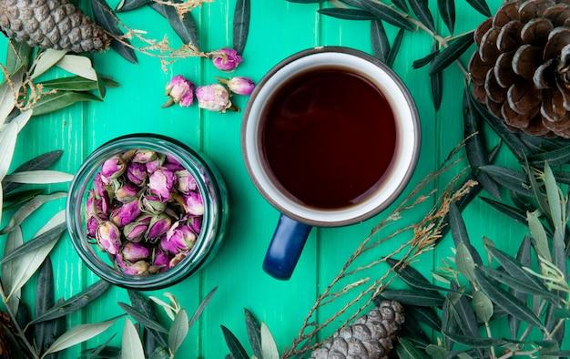 Vista superior de uma caneca de chá com botões de rosa de chá seco em uma jarra de vidro em madeira verde