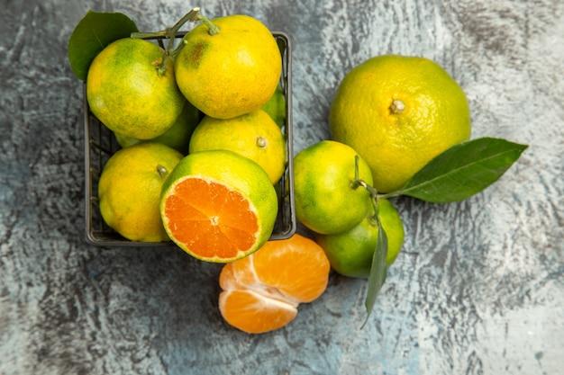 Vista superior de uma cesta com tangerinas verdes frescas cortadas ao meio e tangerina descascada em fundo cinza