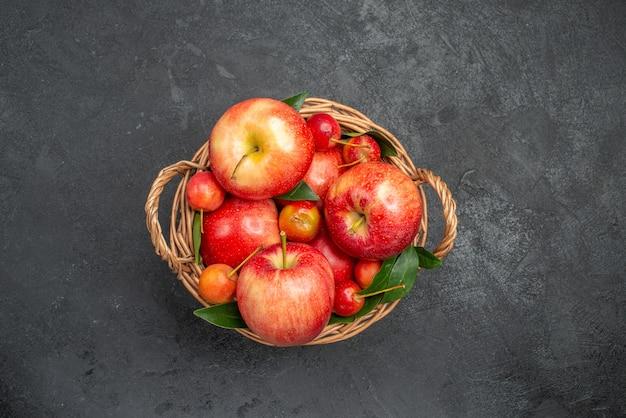 Vista superior de uma cesta de frutas ao longe com cerejas e maçãs na mesa escura