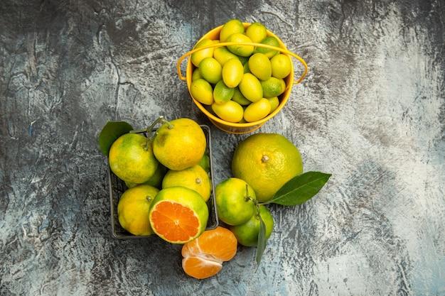 Vista superior de uma cesta e um balde cheio de tangerinas verdes frescas cortadas ao meio e tangerina descascada em fundo cinza