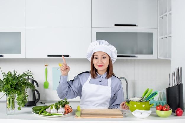 Vista superior de uma chef feminina concentrada sorridente e legumes frescos apontando para cima na cozinha branca