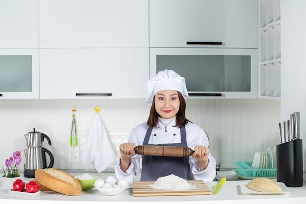 Vista superior de uma chef feminina de uniforme em pé atrás da mesa com uma tábua de cortar alimentos segurando o rolo de massa na cozinha branca