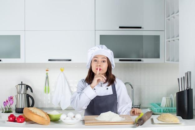 Vista superior de uma chef feminina de uniforme em pé atrás da mesa com uma tábua de pão e legumes fazendo gesto de silêncio