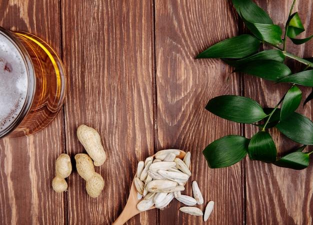 Vista superior de uma colher de madeira com amendoins de sementes de girassol e uma caneca de cerveja em madeira rústica