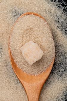 Vista superior de uma colher de pau com açúcar mascavo e cubo de açúcar no fundo de açúcar granulado
