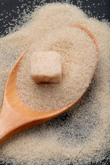 Vista superior de uma colher de pau com açúcar mascavo granulado e cubo de açúcar em fundo preto