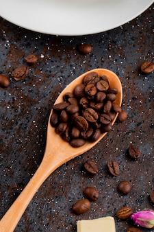 Vista superior de uma colher de pau com grãos de café sobre fundo preto