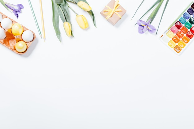Vista superior de uma composição de páscoa: flores, ovos coloridos e tintas aquarela