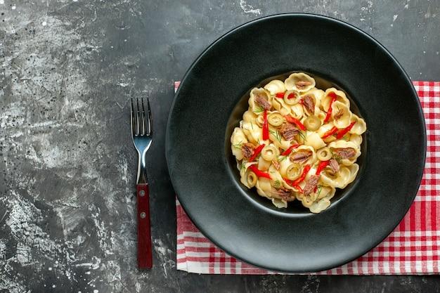 Vista superior de uma deliciosa conchiglie com legumes e verduras em um prato e uma faca na toalha vermelha despojada sobre fundo cinza