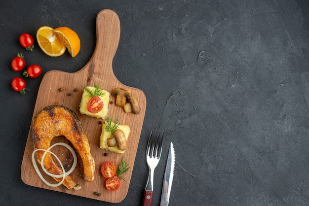Vista superior de uma deliciosa farinha de peixe frito e tomates verdes cogumelos em talheres de tábua de madeira na superfície preta