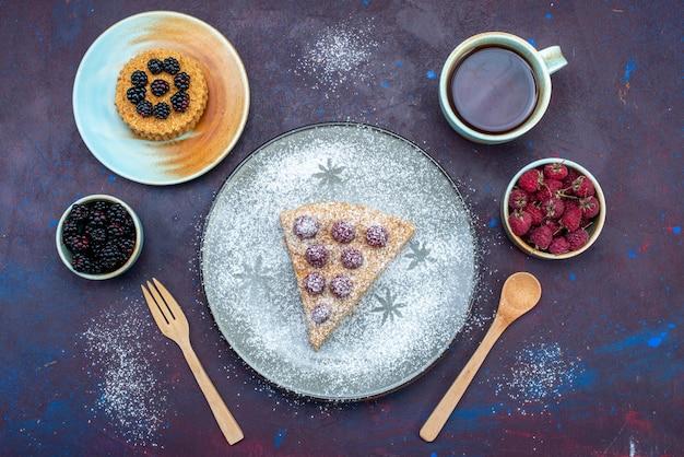 Vista superior de uma deliciosa fatia de bolo com framboesas e chá na superfície escura