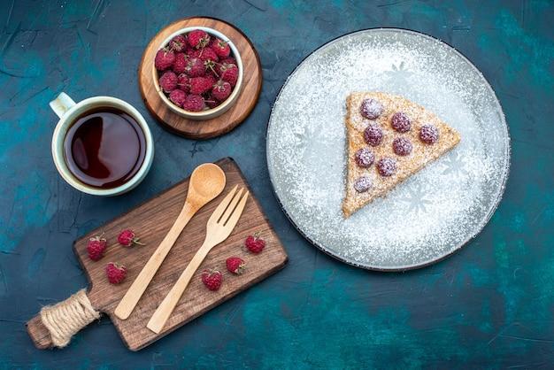 Vista superior de uma deliciosa fatia de bolo com frutas e uma xícara de chá de açúcar em pó na superfície escura