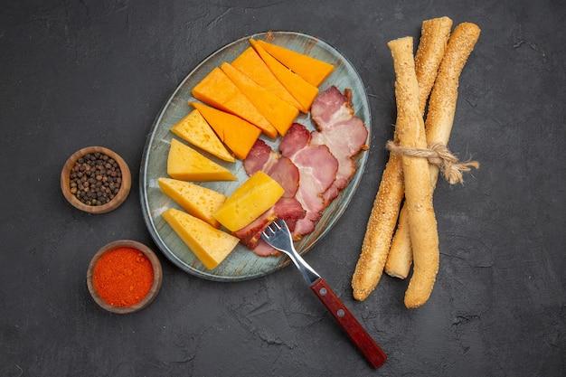 Vista superior de uma deliciosa fatia de salsicha e queijo em um prato azul com pimentas em um fundo escuro