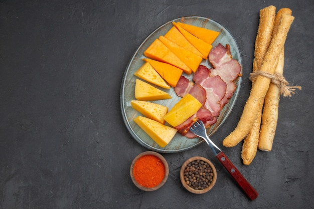 Vista superior de uma deliciosa fatia de salsicha e queijo em um prato azul com pimentas no lado esquerdo em um fundo escuro