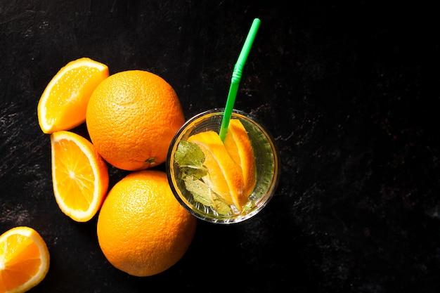 Vista superior de uma deliciosa laranja fria em copos ao lado de frutas orgânicas em fundo escuro de madeira vintage