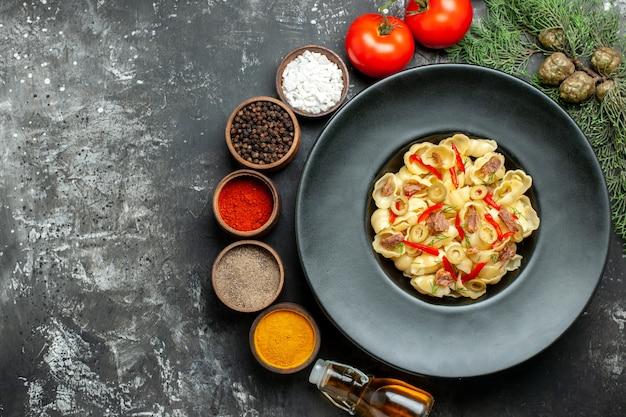 Vista superior de uma deliciosa massa com verduras em um prato e uma faca e uma garrafa de óleo caída de especiarias diferentes na mesa cinza
