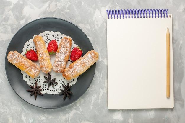 Vista superior de uma deliciosa massa de pão com açúcar em pó com morangos e um bloco de notas na superfície branca Foto gratuita