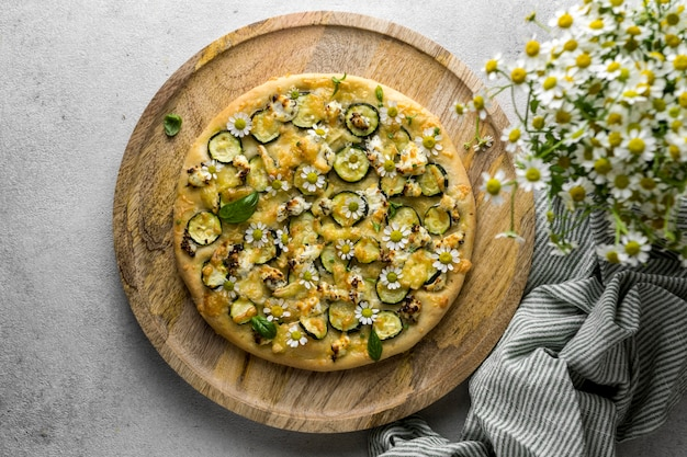 Vista superior de uma deliciosa pizza cozida com buquê de flores de camomila