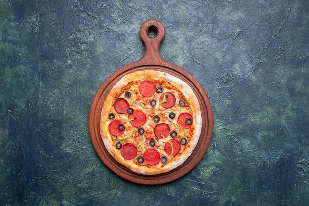 Vista superior de uma deliciosa pizza em uma tábua de madeira sobre uma superfície azul escura