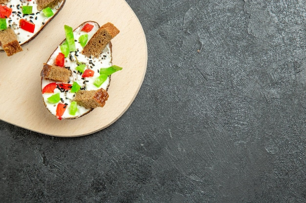 Vista superior de uma deliciosa refeição de abacate com pimentas fatiadas de creme de leite e pedaços de pão na superfície cinza