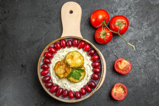 Vista superior de uma deliciosa refeição de abóbora com dogwoods vermelhos frescos e tomates na superfície cinza