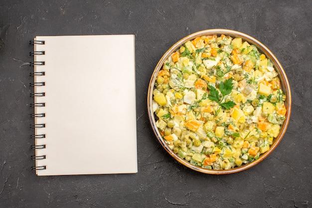Vista superior de uma deliciosa salada com o bloco de notas na superfície escura