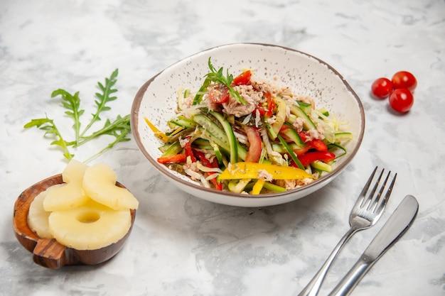 Vista superior de uma deliciosa salada de frango com vegetais, tomates e talheres de abacaxi secos em uma superfície branca manchada