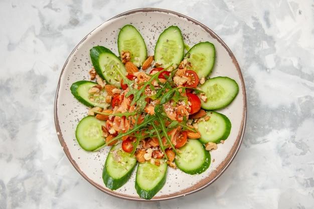 Vista superior de uma deliciosa salada decorada com pepino picado e verduras em uma superfície branca manchada