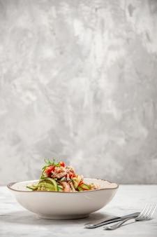Vista superior de uma deliciosa salada em uma tigela branca em uma superfície branca manchada