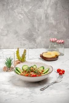 Vista superior de uma deliciosa salada vegana caseira e saudável decorada com pepinos picados em uma tigela, garfo e tomate seco com abacaxi na superfície branca manchada